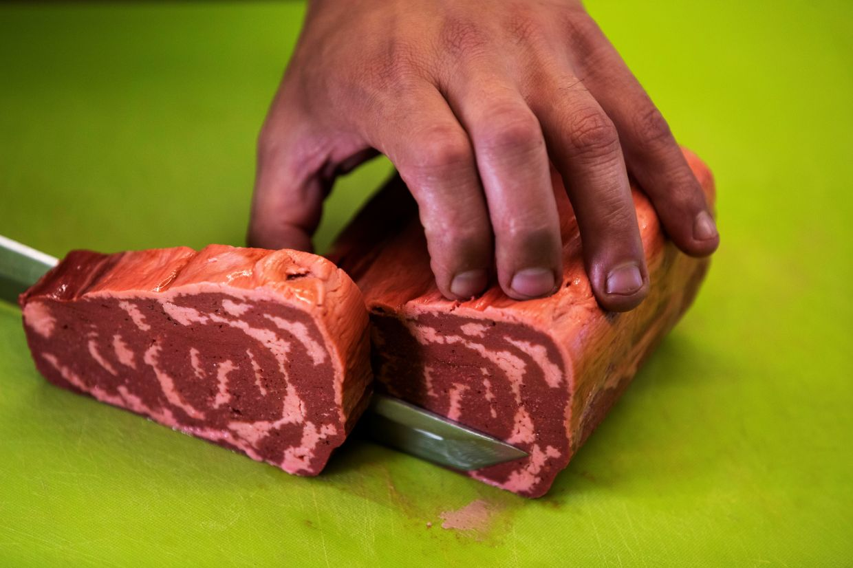 A chef cuts a piece of uncooked 3D printed plant-based steak mimicking real beef and produced by Israeli start-up Redefine Meat.