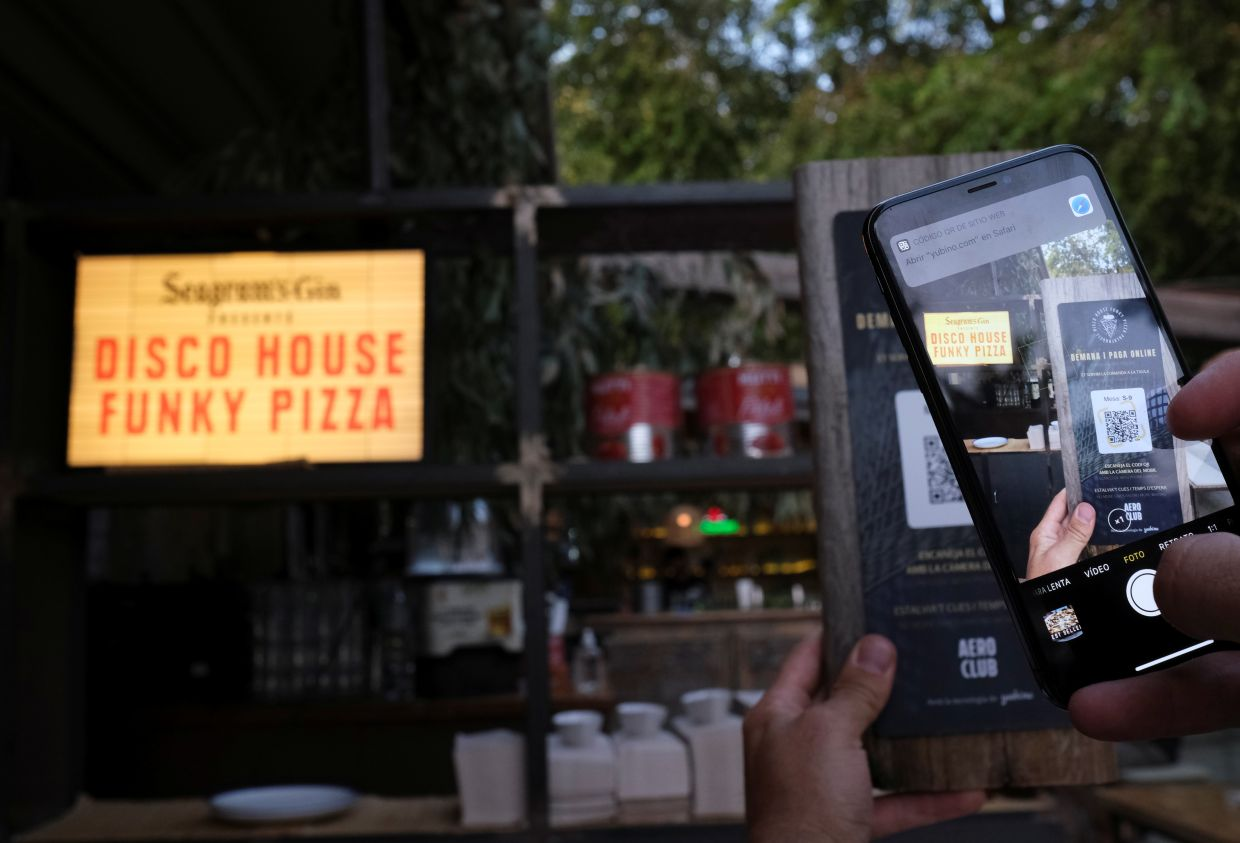 A client using his mobile phone scans the QR code to place an order of a pizza with its ingredients through of the Funky Pay app, where the app replaces waiters at Funky Pizza restaurant in Palafrugell, near Girona, Costa Brava, Spain. — Reuters