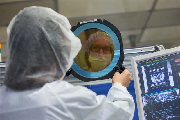 An employee inspects a wafer at the Infineon Technologies AG microchip and sensor manufacturing facility in Regensburg, Germany. Infineon designs, manufactures and markets semiconductors for the automotive, industrial, communications, consumer and security electronics sectors. - Bloomberg filepic