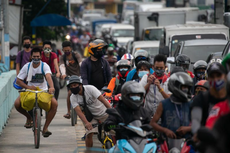 Cyclists bike on the sidewalk as traffic builds up at a checkpoint on the first day of the government's reimplementation of a stricter lockdown to curb virus infections, in Marikina City, Metro Manila, Philippines, on Tuesday, August 4, 2020. - Reuters