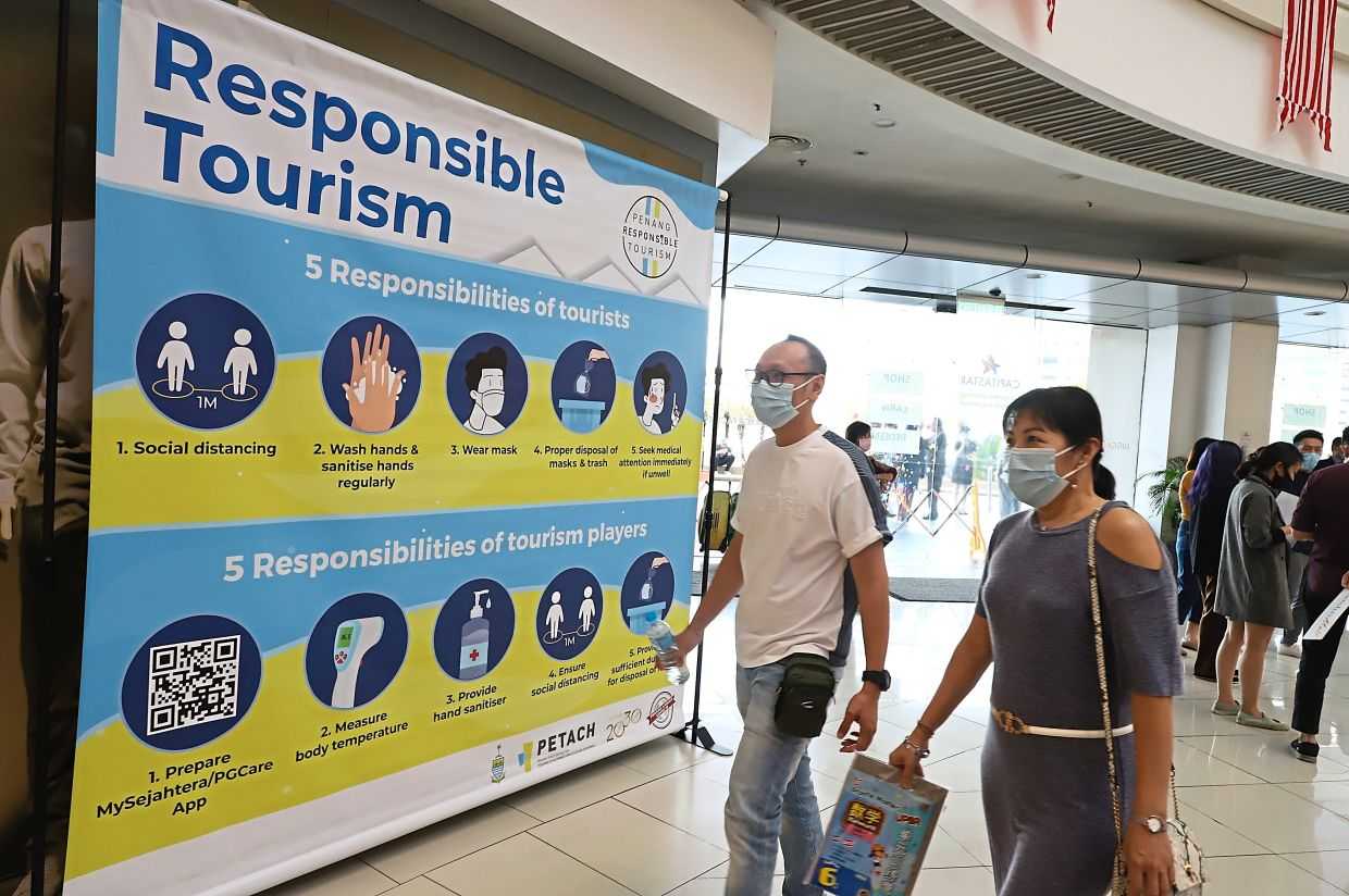 Shoppers at Queensbay Mall walking past the 'Responsible Tourism' logo which outlines the responsibilities of tourists and travel industry players.