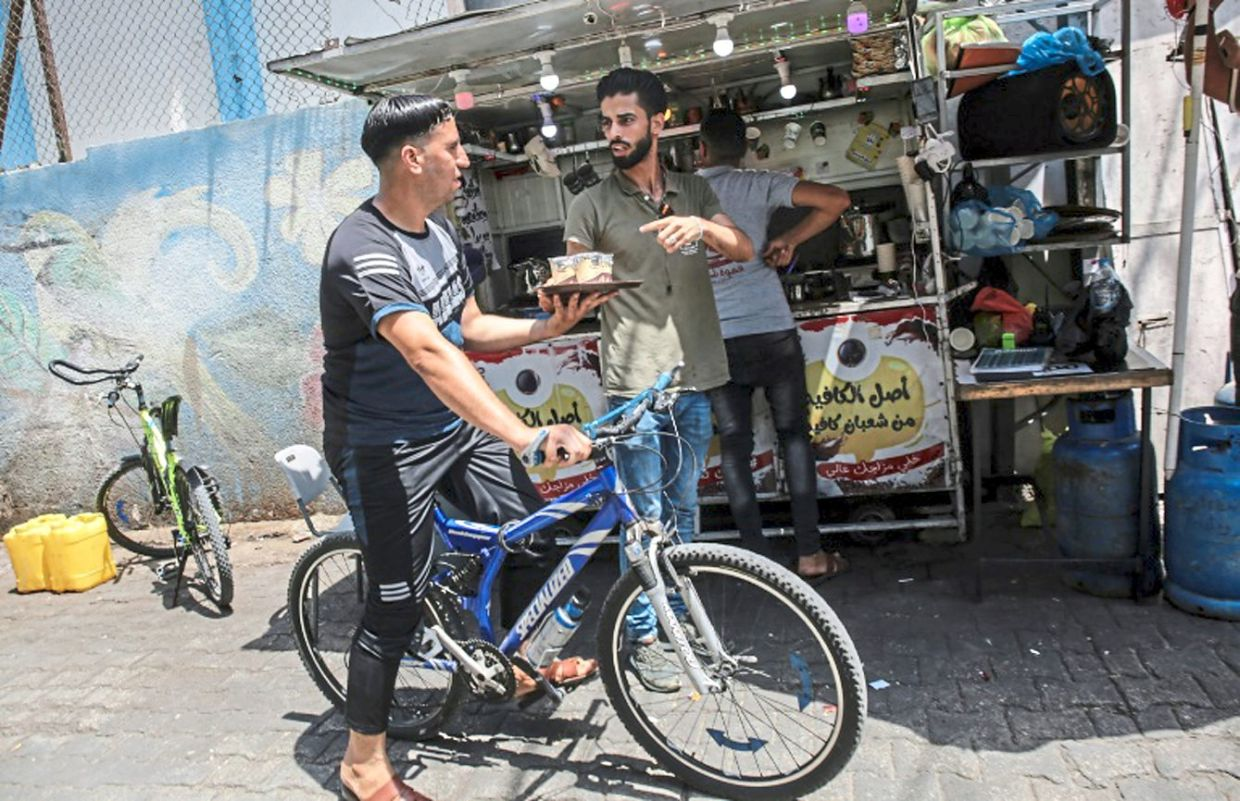 Hamuda launched his two-wheeled hot drink service in May from his small stand near Rafah market, in the southern Gaza Strip.