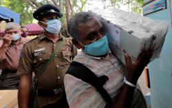 Sri Lankans, wearing masks, flock to voting centres for parliament election