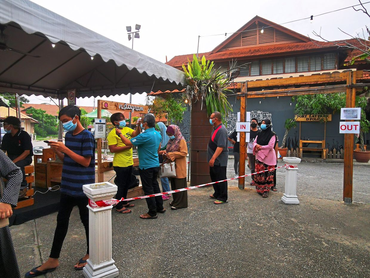 Customers getting their temperature checked and registering via MySejahtera before entering a restaurant.