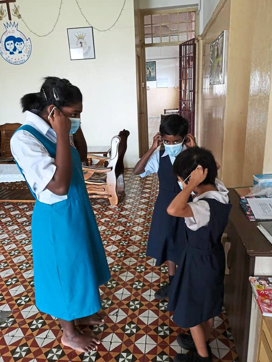 Children at the home  wearing  their masks before going to school.