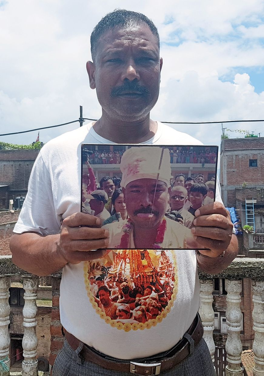 Shrestha holds an old photograph in his hand showing his tongue pierced with an iron needle during the Jibro Chedne Jatra, a tongue piercing festival. The 49-year-old is a local celebrity because he has played the demon at the festival for years.