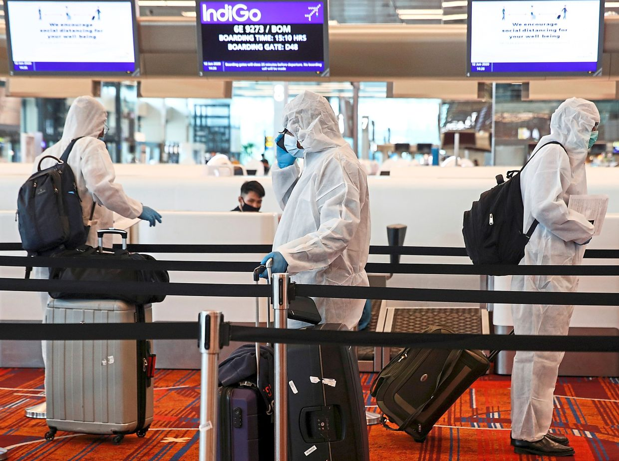 Travellers entering Singapore will be given an electronic monitoring device while they serve a 14-day stay-home notice. — Reuters
