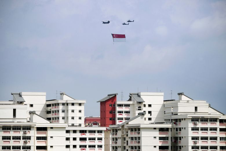 Two Chinook helicopters, each carrying the Singapore flag 1,000ft in the air, flew across the country on two separate routes in the east and the west of the island. - The Straits Times/ANN