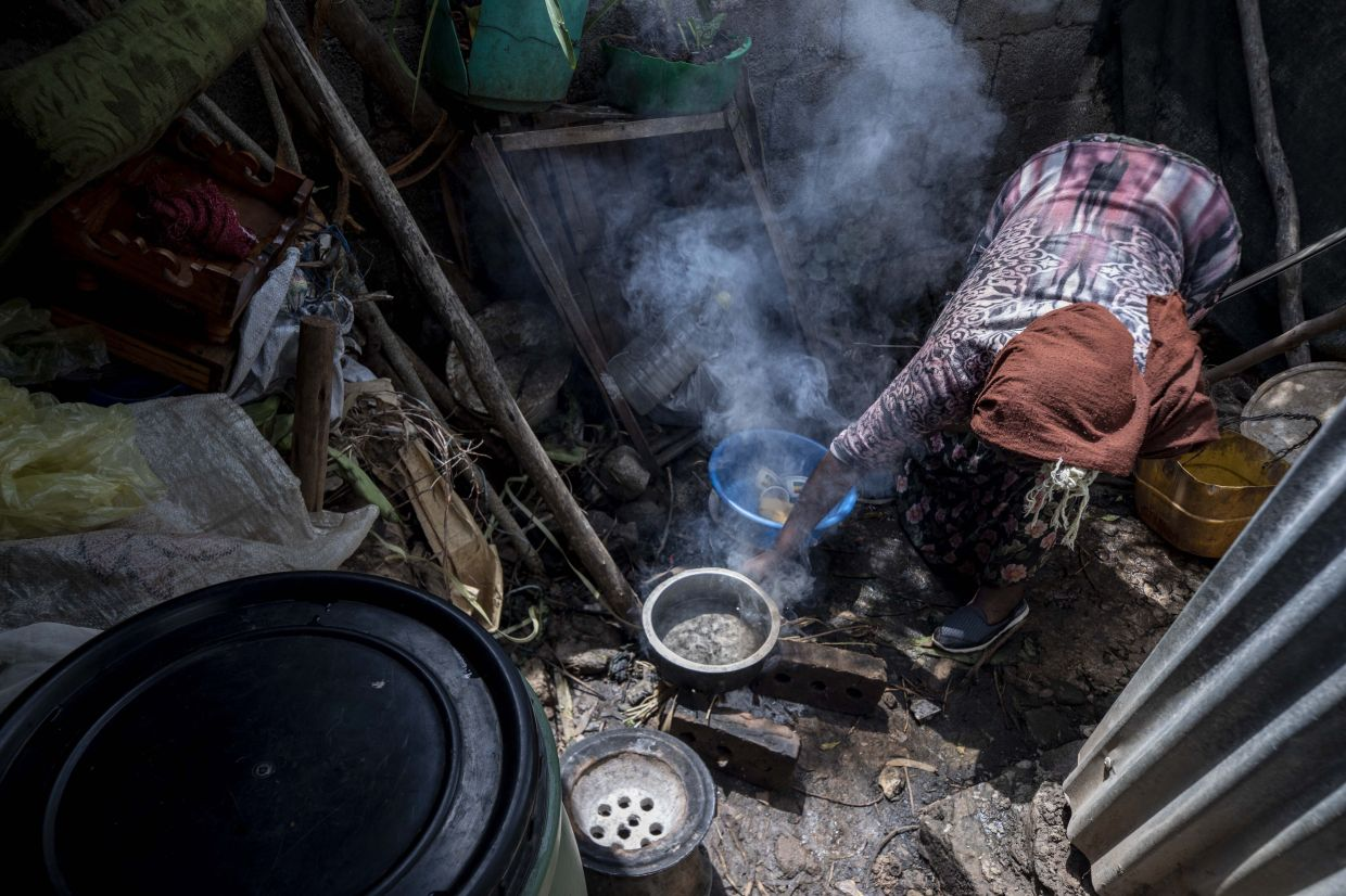 Hailemariam prepares food for her family in her small tent. Photo: AP/Mulugeta Ayene