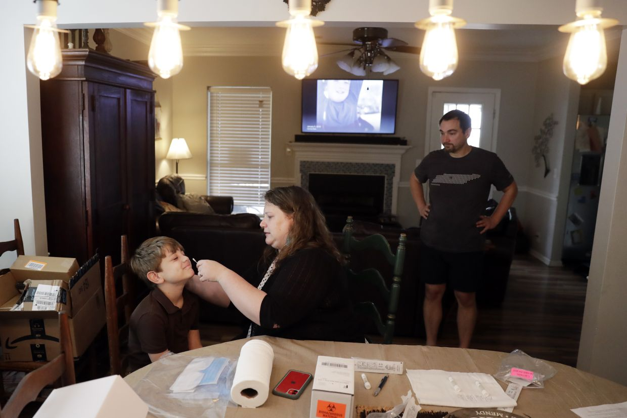 Mendy McNulty (centre) swabs the nose of her son, Hudson, at home, while her husband, Joe, waits his turn. Photo: AP/ Mark Humphrey