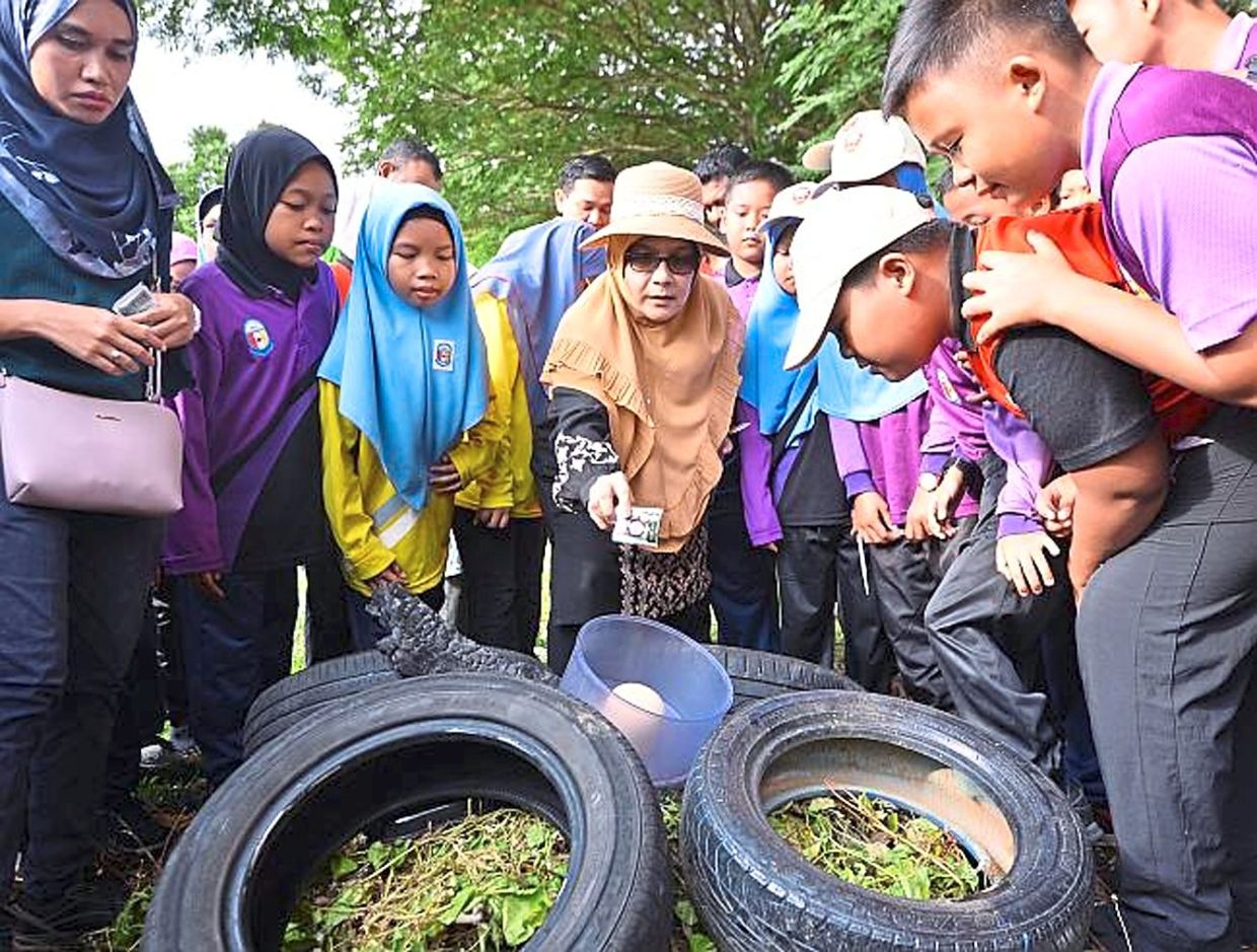 Dr Siti Mariah (centre)  educating schoolchildren on the dangers of having  stagnant water in their homes as it provides breeding ground for Aedes  mosquitoes. — Photos: LOW LAY PHON/The Star