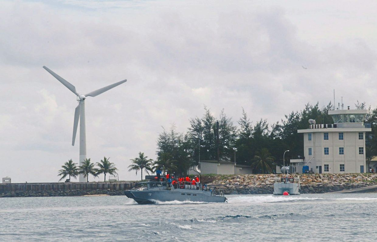 A Royal Malaysian Navy fast patrol boat speeds off from Pulau Layang Layang. The wind turbine supplies additional electrical power to the navy base on the island.
