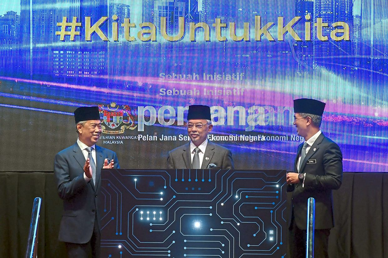 Towards a better future:Sultan Abdullah (centre) witnessing the launch of the sukuk Prihatin fund at the Finance Ministry. Looking on is Muhyiddin (left) and Zafrul. — Bernama