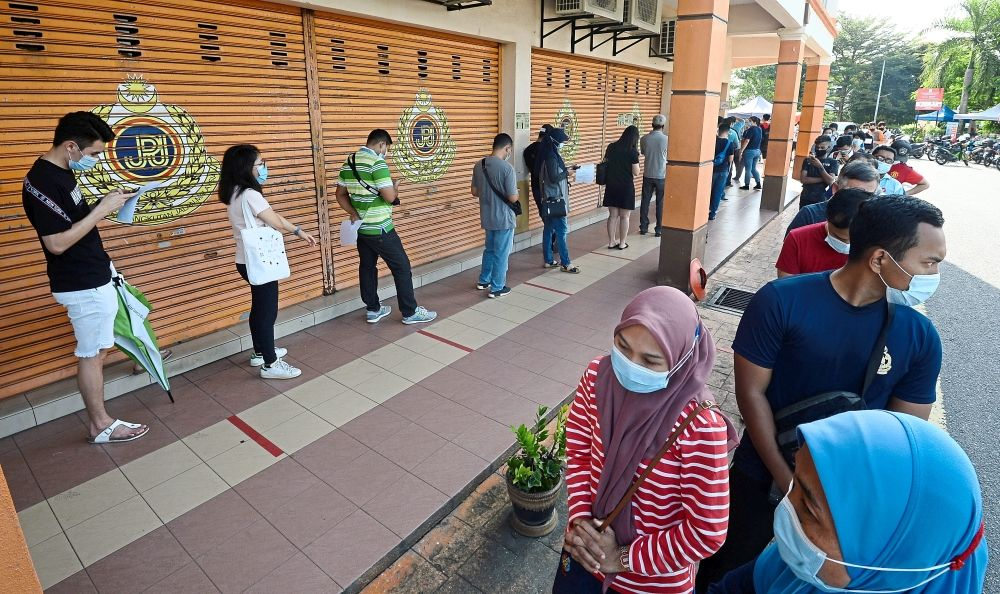 Beating the deadline: People queuing up outside the Road Transport Department branch in Bandar Baru Bangi. Only a limited number of visitors are allowed in at a time as part of the preventative measures against the spread of Covid-19. — AZHAR MAHFOF/The Star