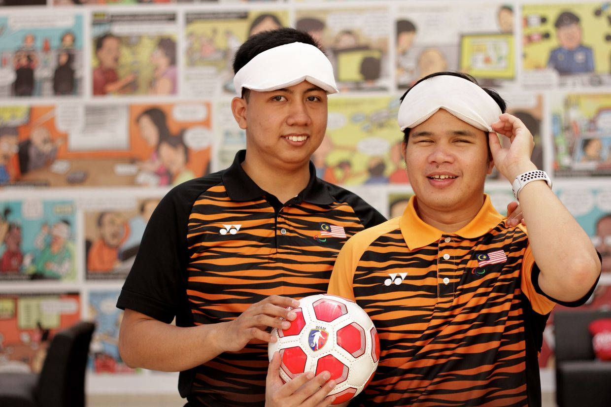 Rollen (right) and Asri are members of the Malaysian blind football team.