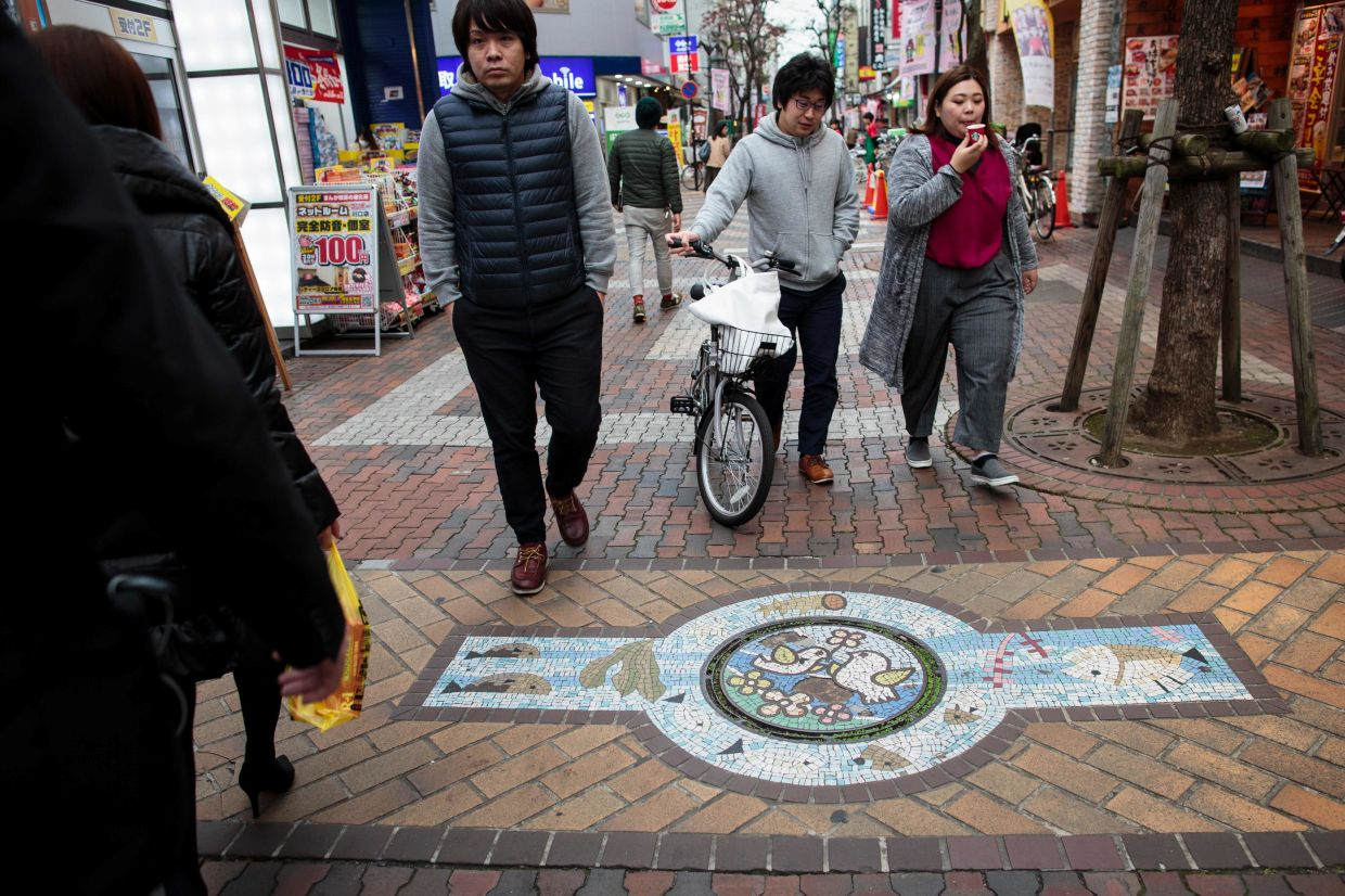 Japan's sewerage industry has found a way to clean up its dirty and smelly image: elaborately designed and colourful manhole covers with 12,000 local varieties nationwide - including, of course, a Hello Kitty design. Photo: AFP