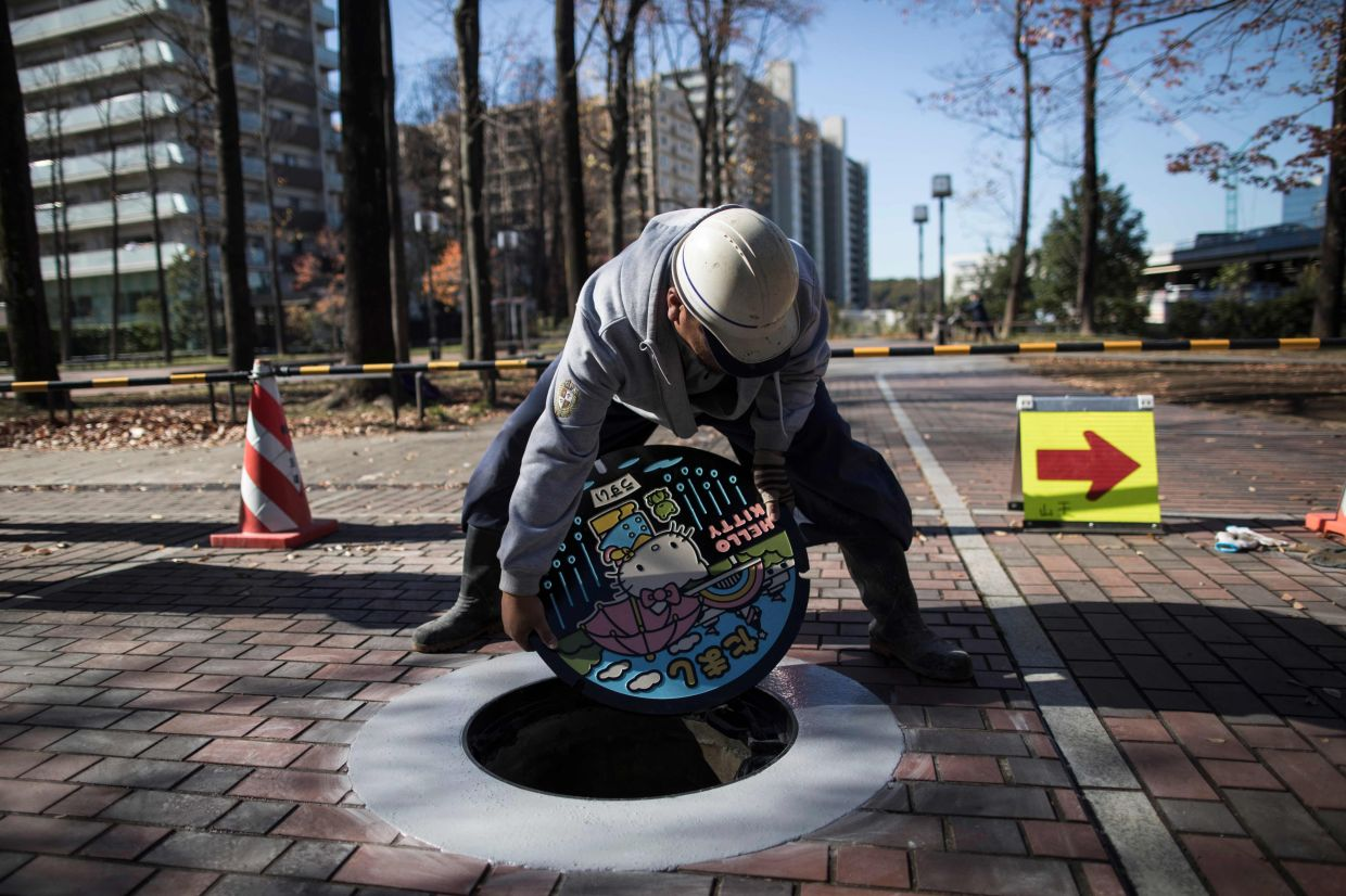 In this picture taken on November 21,2017 a worker installs a new manhole, with a design bearing Japanese charachter