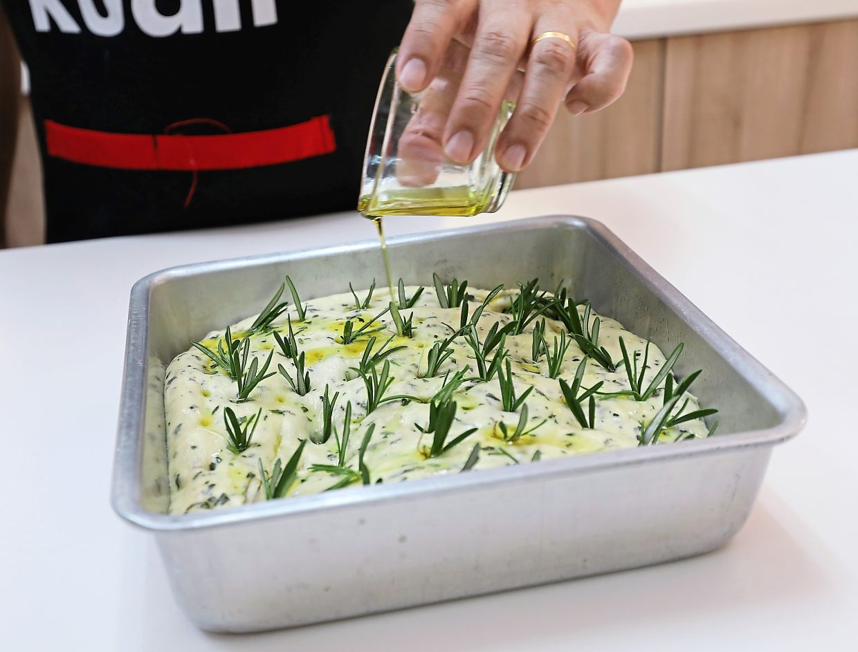 After inserting rosemary fronds into the dough, drizzle with extra virgin olive oil and sprinkle with Maldon sea salt.