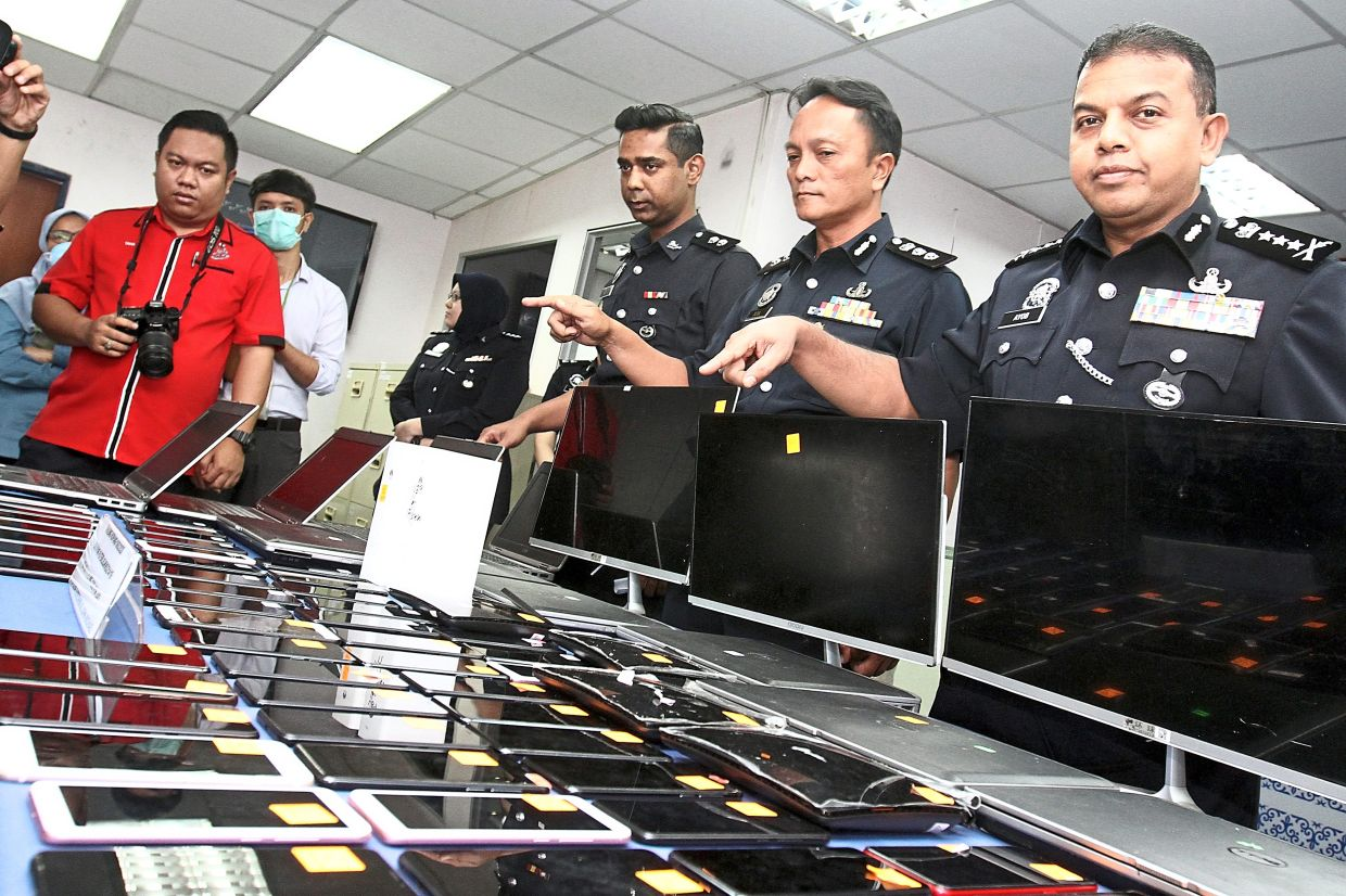 Comm Ayob Khan (right) showing seized electronics that were used to run a Macau scam operation in Johor. — Filepic
