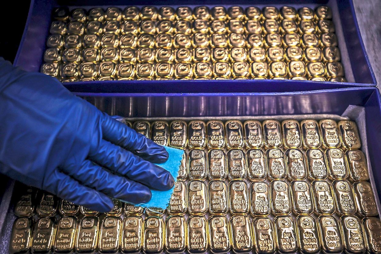 A worker polishes gold bullion bars at the ABC Refinery in Sydney. Gold prices hit US$2,000 an ounce on markets for the first time on August 4, the latest surge in a commodity seen as a refuge amid economic uncertainty. — AFP