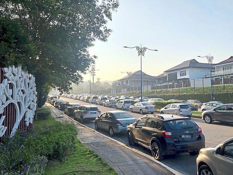 A high number of vehicles parked on both sides of the road near the Shah Alam Community Forest every weekend.