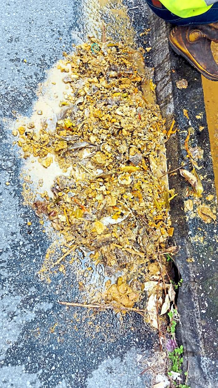 The food waste and grease scooped up by MBI cleaners at a clogged drain along a lane off Jalan Raja Permaisuri Bainun.