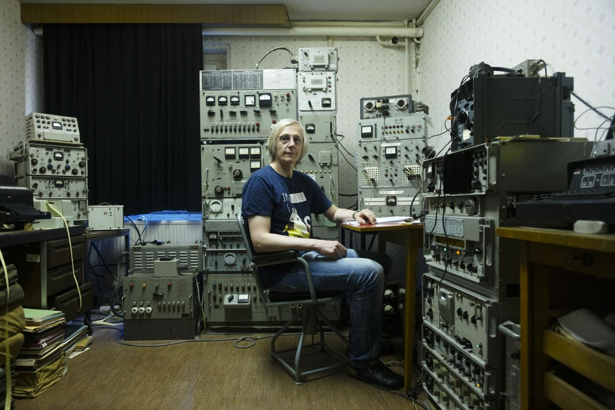 Raeder sits between carefully restored Soviet shortwave transmitter he use for communication with military radio enthusiasts around the world in the village Harnekop at a rural region east of Berlin, Germany.