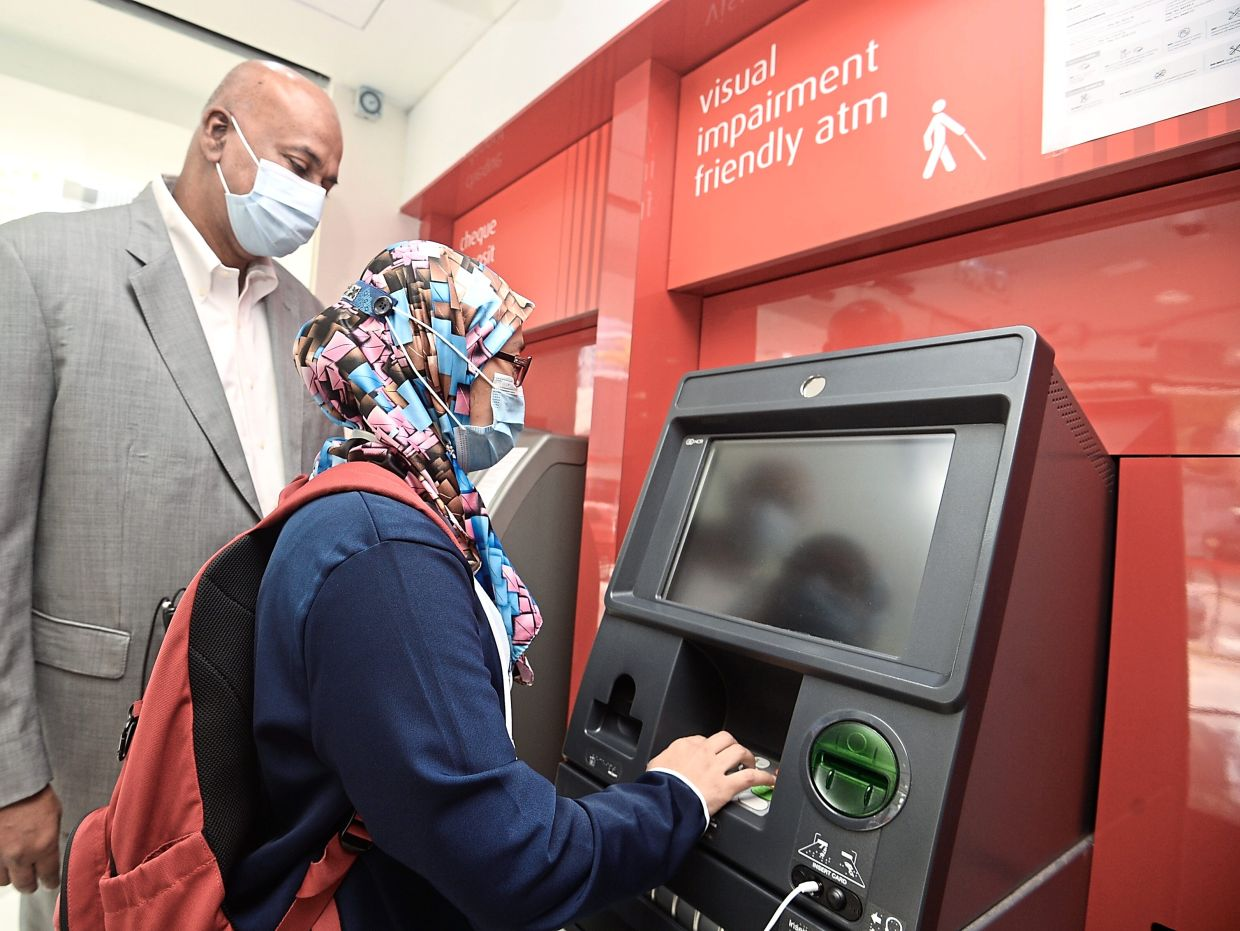 Mascrinas (left) observing how a visually impaired person uses the talking ATM to perform a banking transaction.