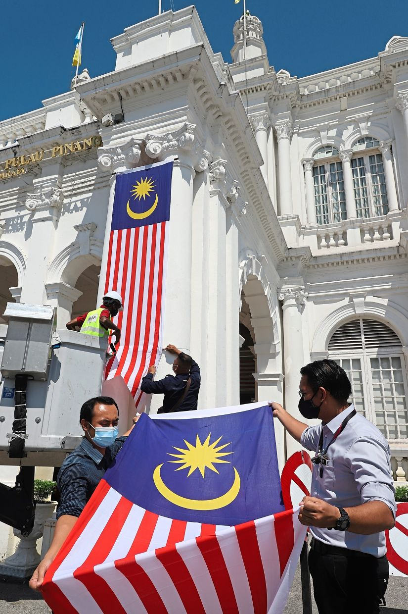 Patriotic display: Jazmi (right) with City Hall admin assistant Muhammad Hairi Sady Hashim straightening out a Jalur Gemilang streamer to be put up at the City Hall in George Town, Penang. — LIM BENG TATT/The Star