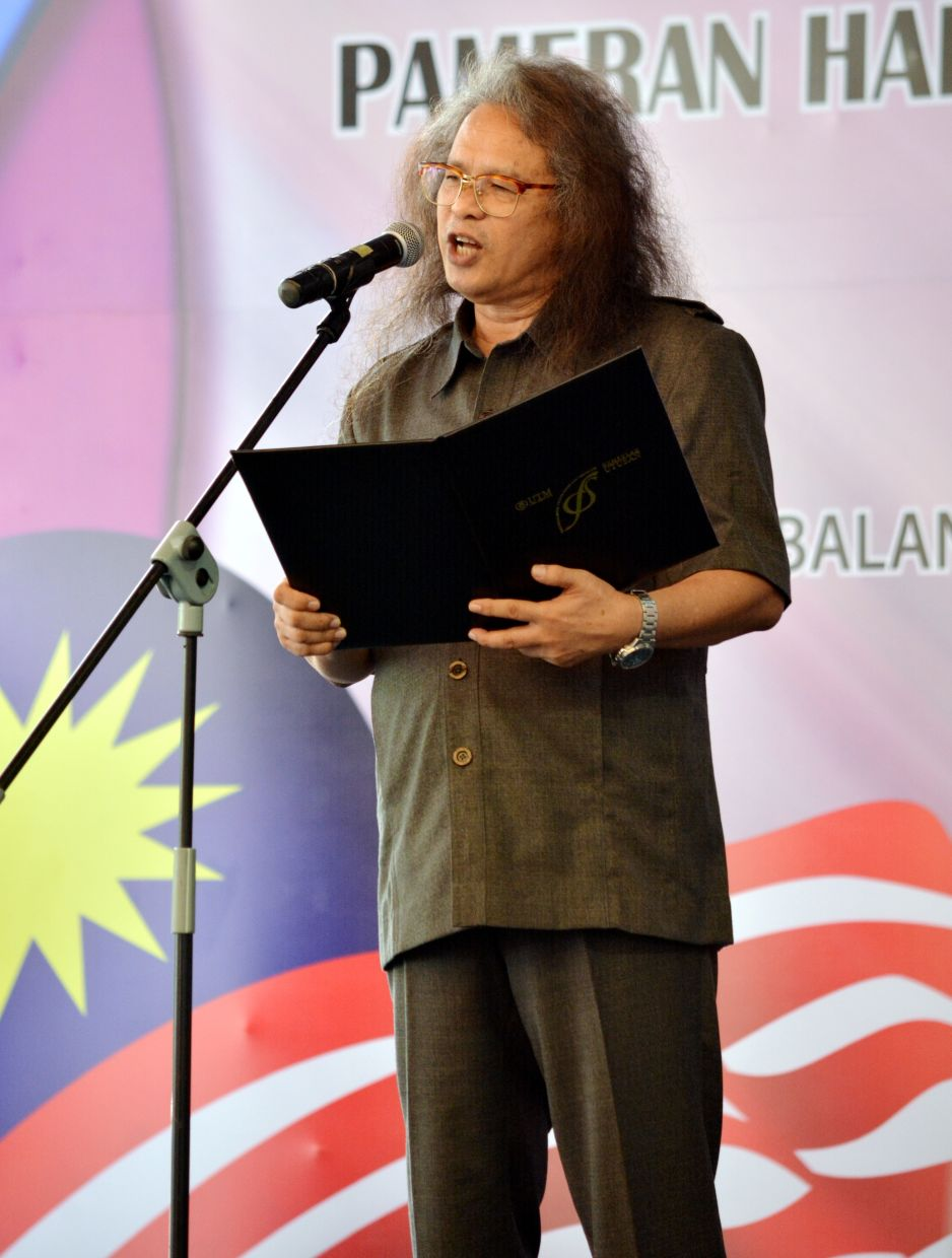 """A file photo of Lim reciting a poem at the launch of the """"One Malaysia, One Story"""" exhibition at the National Museum in 2016 in conjunction with National Day."""
