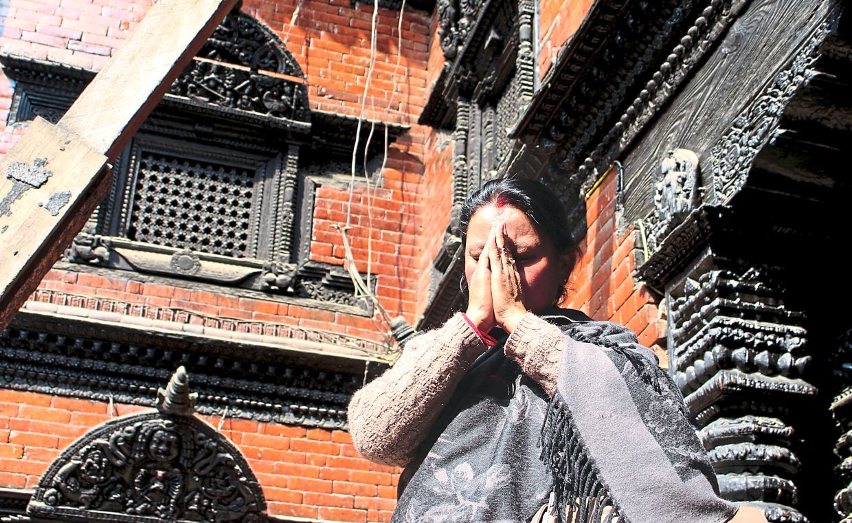 A visitor prays for happiness during a visit to a Nepalese kumari house.