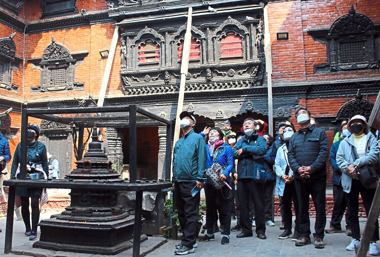 A group of tourists visiting Nepal waits for the kumari to appear at her window.