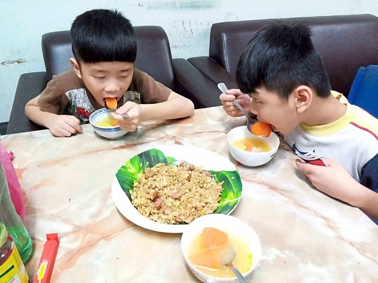 Hanson, 13, one of the children who took part in the UNICEF-UNFPA study, photographs his younger brothers eating the lunch cooked by him. Photo: UNICEF