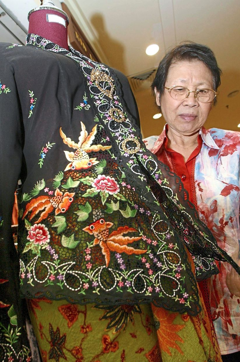 The late Lim, here showing off a goldfish-themed nyonya kebaya which she designed, received many accolades for her work.