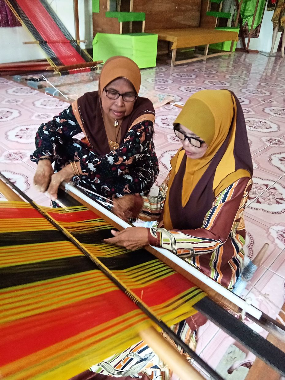 Pandian patiently teaching a student on the techniques of weaving a Dastar cloth. Photo: Abdul Kalam Mukim