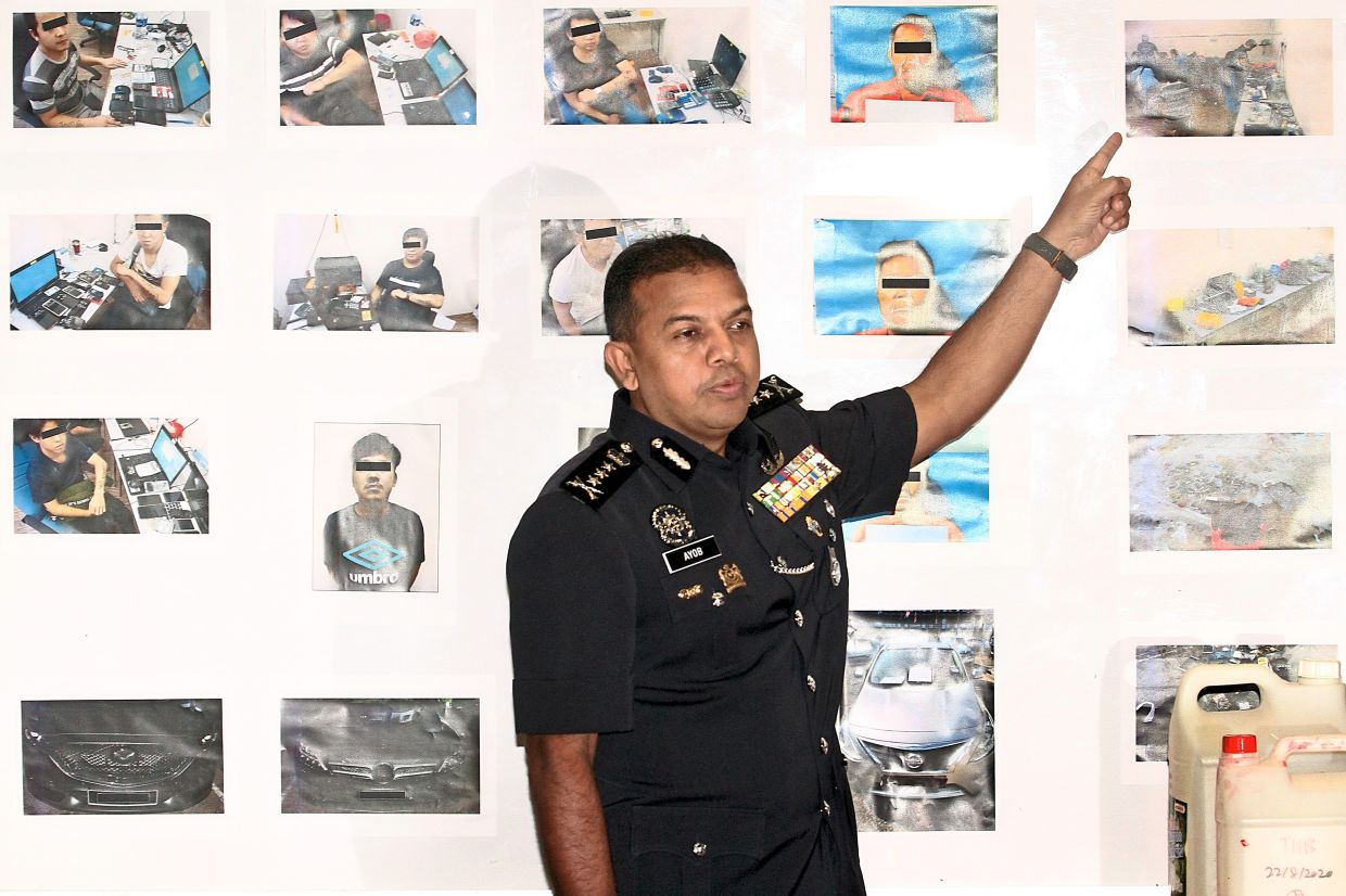 Putting a face to the crime: Comm Ayob showing photos of loan sharks during a press conference at the state police headquarters in Johor Baru. — THOMAS YONG/The Star
