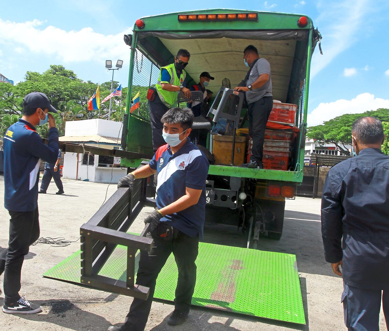 Enforcement officers unloading seized items from a vehicle at the storage facility in Cheras.