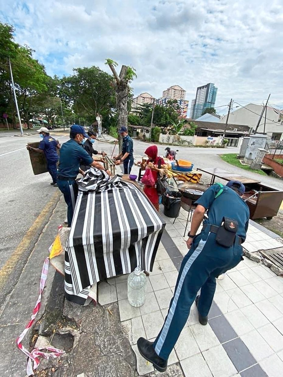 Enforcement officers dismantling an illegal stall in Kuala Lumpur that is blocking a five-foot way.