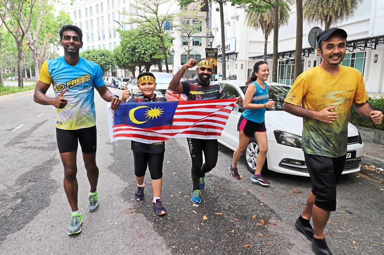 Participants running with the Malaysian flag.