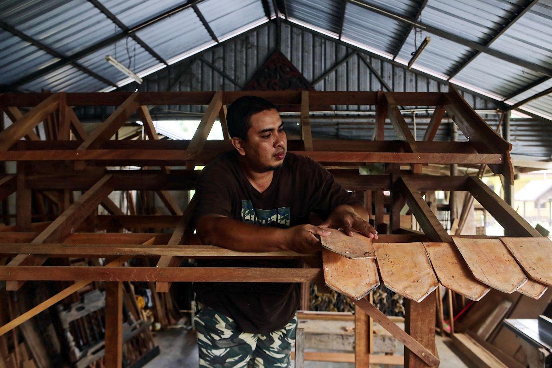 A worker arranges a series of singhora roof tiles to a gazebo. Photo: Bernama