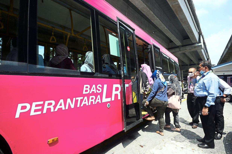 Pretty in pink:Passengers boarding a LRT feeder bus in Wangsa Maju.