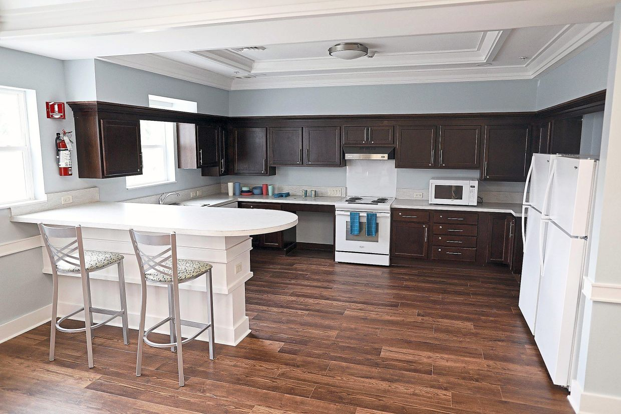 A shared kitchen space features lots of room for gathering and storing food in the fridges.