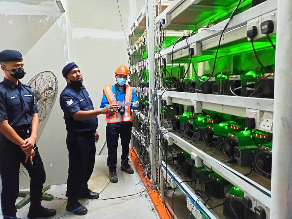 Authorities checking on the cryptocurrency mining machines during a raid in Iskandar Puteri. — VENESA DEVI/The Star