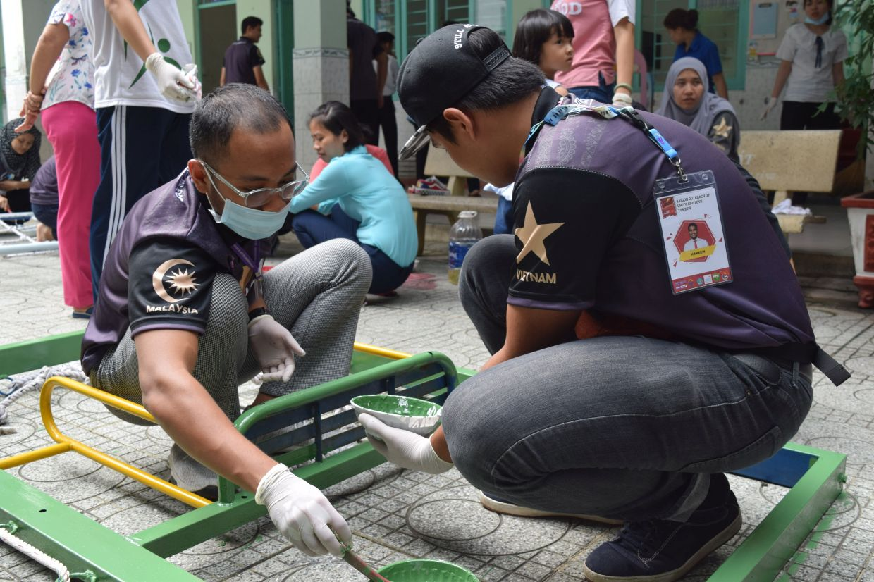 University of Cyberjaya' students repainting and repairing equipments at the Bin Minh School at the International Humanitarian Mission to Saigon, Vietnam in 2019.