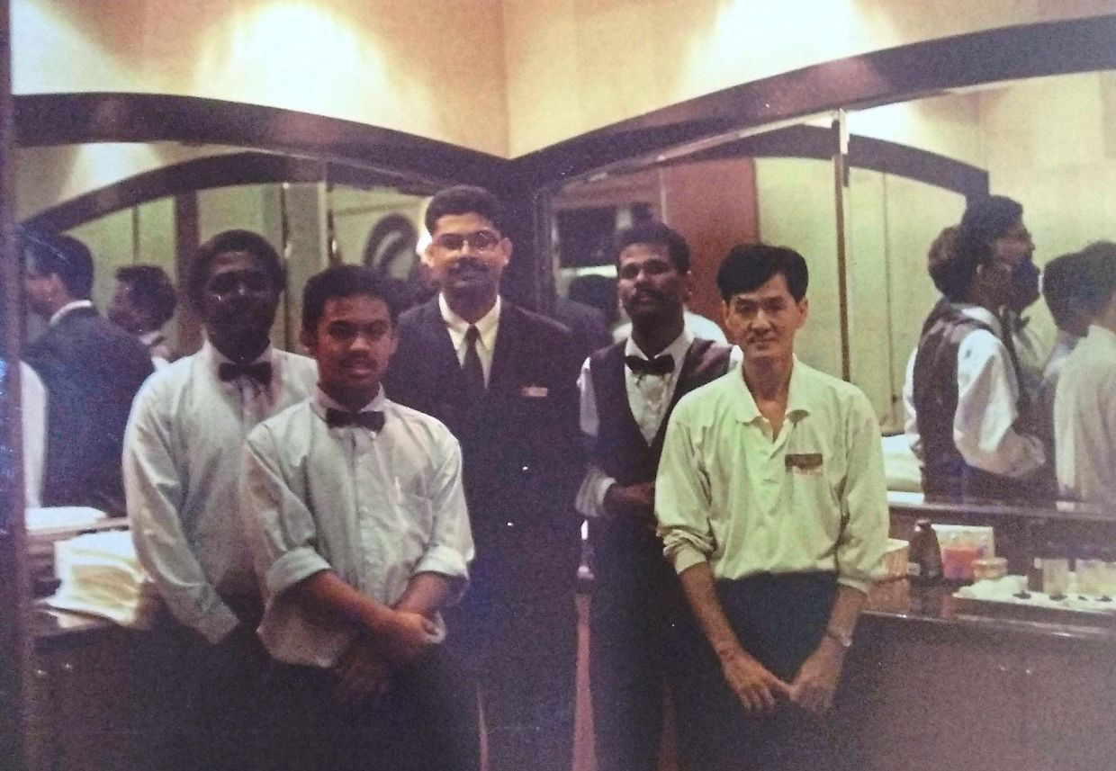 A teenaged Imran (bow tie, in front) posing with his multi-ethic co-workers and supervisor.