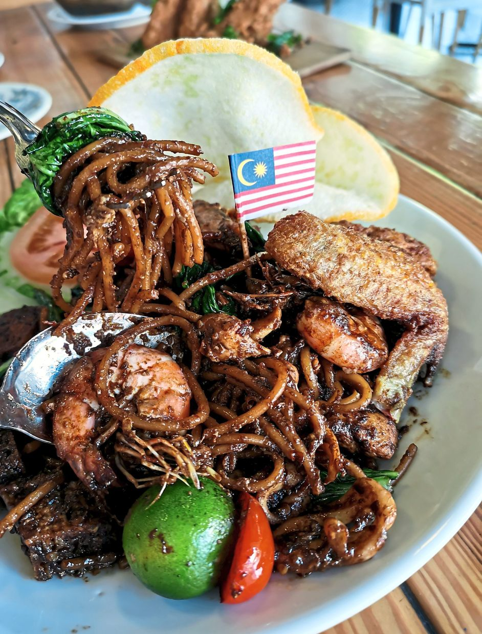 Pasta Goreng Mamak served with seafood, fried chicken and crackers.