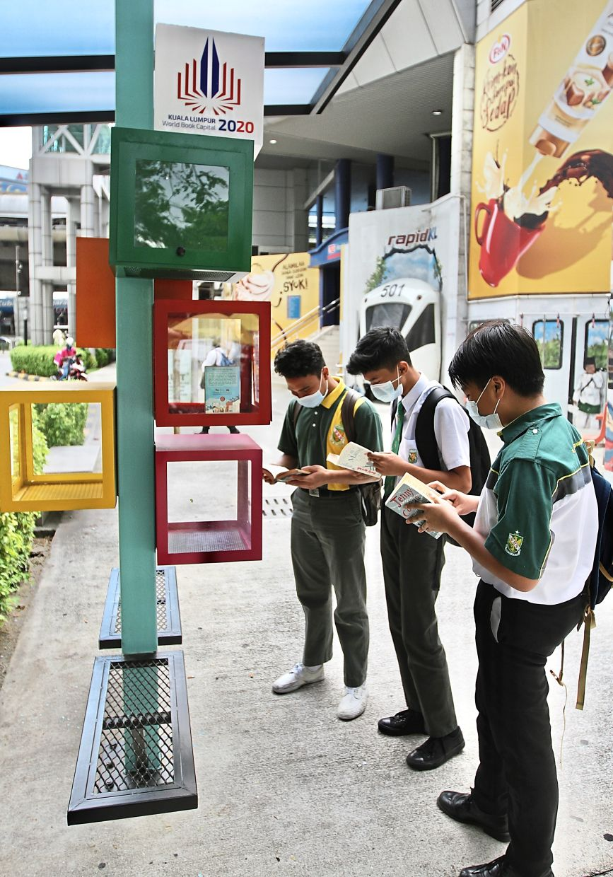 A group of students using the book kiosk located  on Jalan Tun Perak the right way.