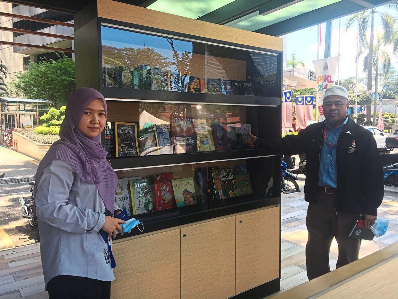 Mohd Fadzil (right) and Emilea at the book kiosk set up at the Menara 3 DBKL bus stop on Jalan Raja Abdullah in Kuala Lumpur. — Photos: LOW BOON TAT/The Star