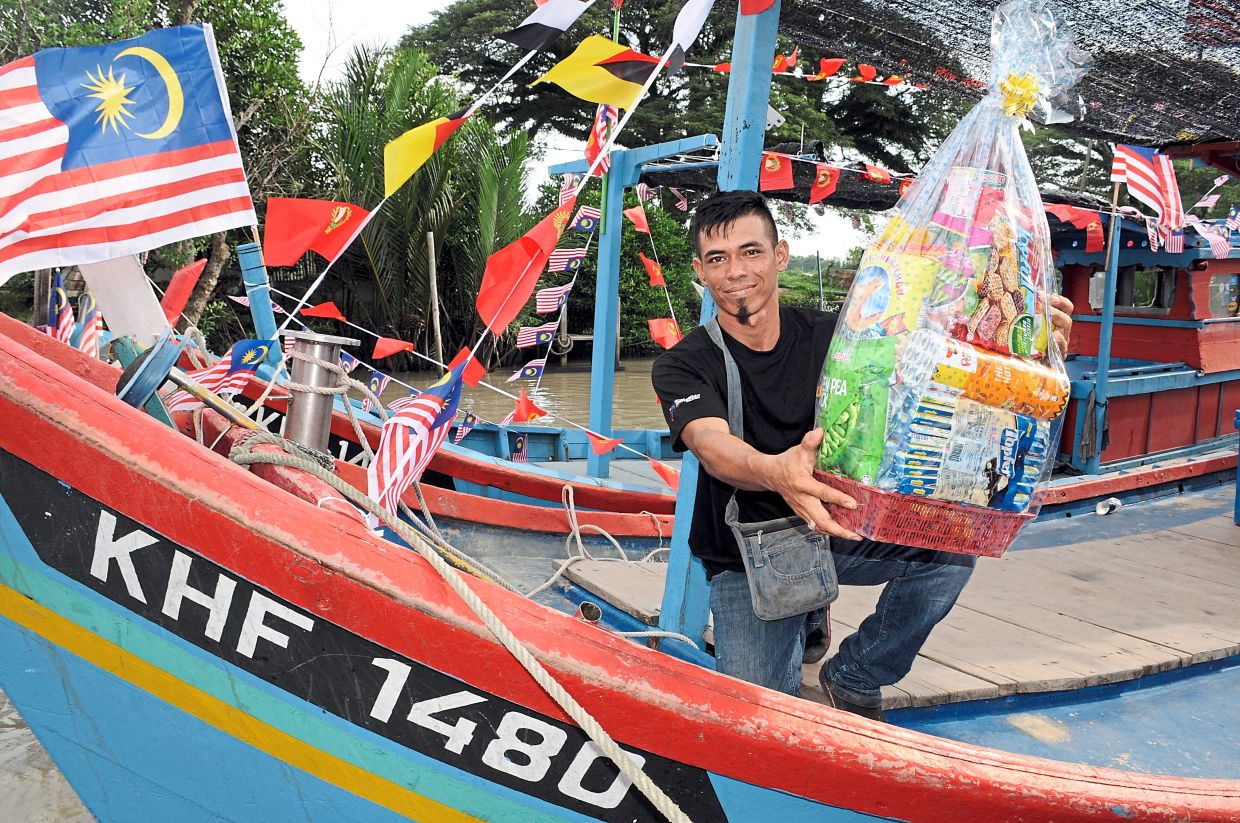 Mohd Khairul showing the hamper he won besides a RM150 cash prize after emerging as  the first prize winner in the boat decorating competition.
