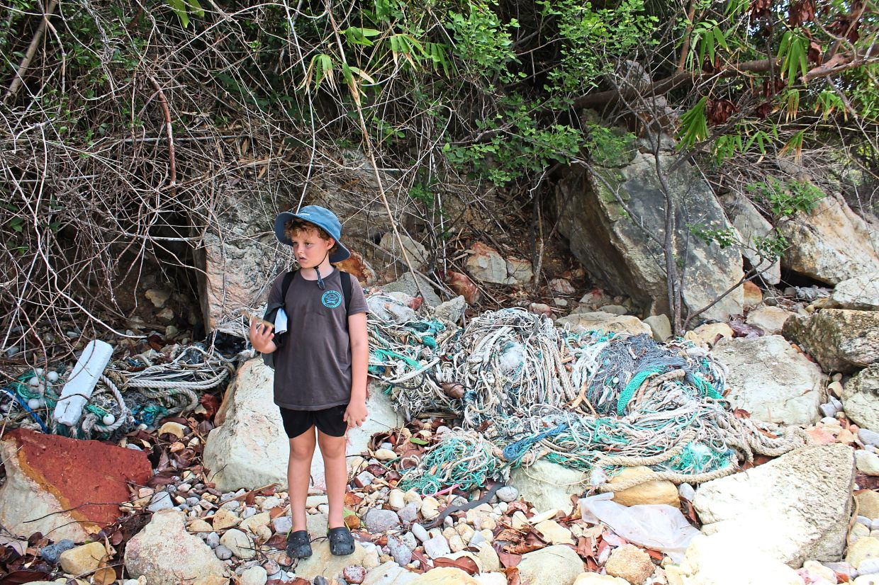 Indi surrounded by plastic waste on a beach in Tioman Island.